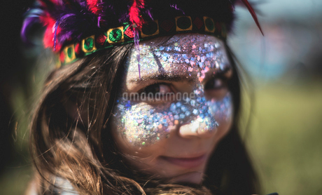Young woman at a summer music festival face painted, wearing feather headdress, looking at camera.の写真素材 [FYI02858659]