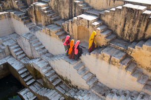 High angle view of four women wearing saris walking up stairwell around water pool of an ancient buiの写真素材 [FYI02858667]