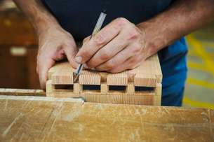Close up of person working a boat-builder's workshop, joining together two pieces of wood.の写真素材 [FYI02858672]