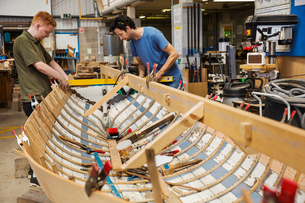 Two men in a boat-builder's workshop, working together on a wooden boat hull.の写真素材 [FYI02858697]