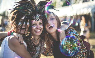 Three young women at a summer music festival wearing feather headdress and faces painted, smiling atの写真素材 [FYI02858700]
