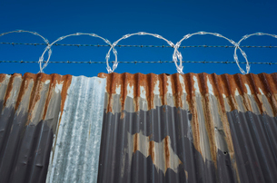 Low angle view of worn corrugated metal fence, razor wire above.の写真素材 [FYI02858701]