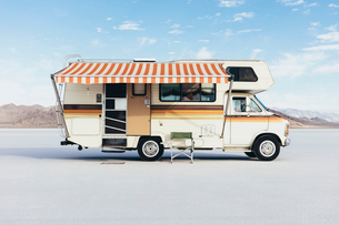 Vintage Dodge Sportsman RV with striped canopy parked on Salt Flatsの写真素材 [FYI02858712]