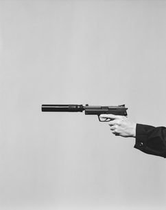 Detail of man aiming high powered hand gun with silencerの写真素材 [FYI02858714]