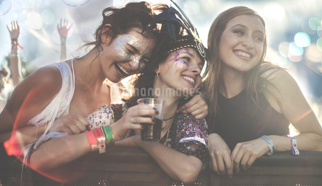 Three young women at a summer music festival wearing feather headdress and faces painted, smiling anの写真素材 [FYI02858725]