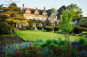 Exterior view of a 17th century historic Cotswolds country house from a garden with flower beds, shrの写真素材 [FYI02858727]