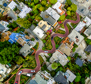Aerial view of a residential city area, with road descending a hillside with eight hairpin turns.の写真素材 [FYI02858734]