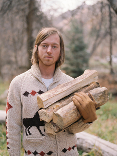 Young blond man carrying firewood.の写真素材 [FYI02858746]