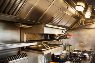 Interior view of restaurant kitchen, pots on stovetop, grill and extractor hood.の写真素材 [FYI02858763]