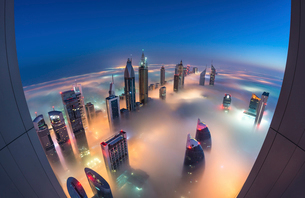 Aerial view of cityscape with illuminated skyscrapers above the clouds in Dubai, United Arab Emirateの写真素材 [FYI02858768]