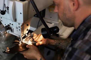 A man using an industrial sewing machine, stitching leather handmade goods.の写真素材 [FYI02858772]