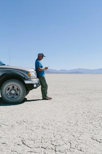 Man leaving against truck in desert, using smart phone, Black Rock Desert, Nevadaの写真素材 [FYI02858775]