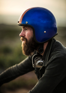 Profile of bearded man wearing blue open face crash helmet, goggles round his neck.の写真素材 [FYI02858782]