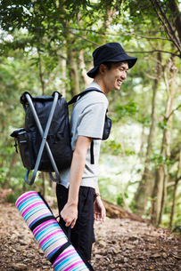 Man standing in a forest, carrying a picnic rug and backpack.の写真素材 [FYI02858786]