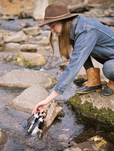 Young blond woman wearing a hat, putting drink bottles in a river.の写真素材 [FYI02858797]