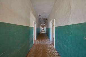 A view down a long corridor in a deserted derelict building full of sand.の写真素材 [FYI02858799]
