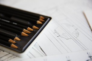 Close up of design drawings for furniture and a tray of pencils.の写真素材 [FYI02858800]