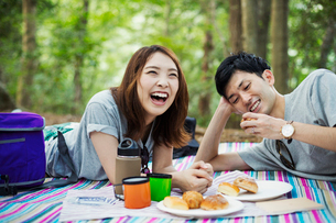 Young woman and man having a picnic in a forest.の写真素材 [FYI02858818]