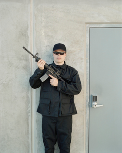 Man wearing special forces uniform and holding high powered semi-automatic rifle, guarding doorwayの写真素材 [FYI02858819]