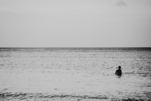 View across the Andaman Sea from Ko Lanta Yai, a person swimming in a vast oceanの写真素材 [FYI02858827]
