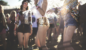 Young woman at a summer music festival wearing golden sequinned hot pants, dancing among the crowd.の写真素材 [FYI02858831]