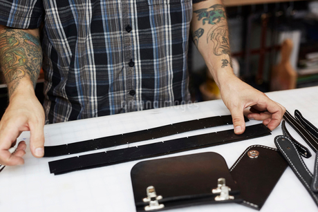 A man with tattooed arms, craftsman working at a bench, smoothing strips of tanned coloured leather.の写真素材 [FYI02858835]