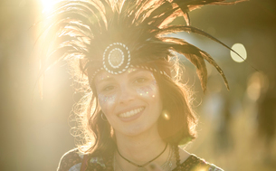 Young woman at a summer music festival wearing feather headdress and face painted, smiling at cameraの写真素材 [FYI02858838]