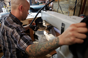 A leather worker, craftsman using an industrial sewing machine on leather material, making a bag.の写真素材 [FYI02858840]