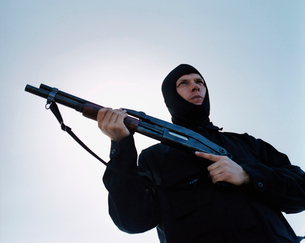 Man holding high powered shotgun, wearing special forces uniform and balaclavaの写真素材 [FYI02858847]
