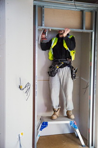 A carpenter in a small space fitting a shelf into a wall cupboard.の写真素材 [FYI02858852]