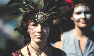 Young woman at a summer music festival face painted, wearing feather headdress, looking at camera.の写真素材 [FYI02858856]