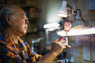 A senior craftsman at work in a glass maker's studio workshop, in inspecting red wine glass with cutの写真素材 [FYI02858861]