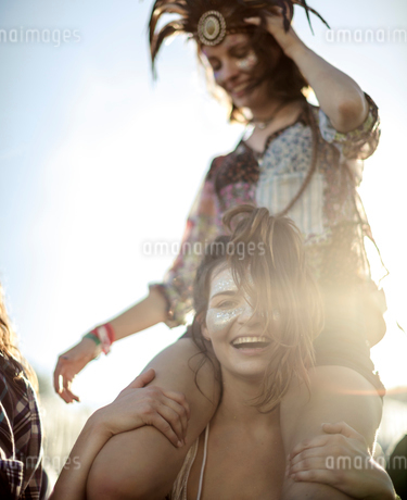 Young woman at a summer music festival carrying a friend on her shoulders, face painted, smiling atの写真素材 [FYI02858862]