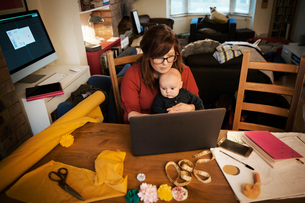 A woman seated with her baby on her lap, multitasking and using a laptop.の写真素材 [FYI02858865]