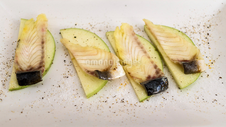 High angle close up of grilled mackerel on slices of apple.の写真素材 [FYI02858873]