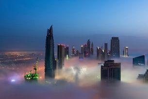 View of illuminated skyscrapers above the clouds in Dubai, United Arab Emirates.の写真素材 [FYI02858879]