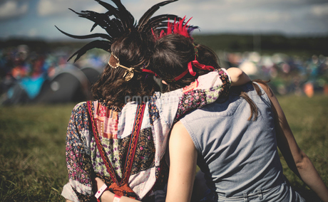 Rear view of two young women at a summer music festival wearing feather headdresses, arm around shouの写真素材 [FYI02858896]