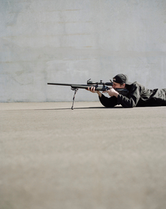Man aiming high powered rifle, in sniper positionの写真素材 [FYI02858903]