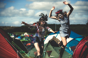 Two smiling young women at a summer music festival face painted, wearing feather headdress, jumpingの写真素材 [FYI02858912]