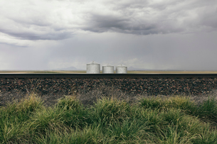 Grain silos and storm clouds over vast farmland and prairie, train tracks in foregroundの写真素材 [FYI02858943]