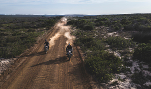 Landscape with two men riding cafe racer motorcycles in circles on a dusty dirt road.の写真素材 [FYI02858945]