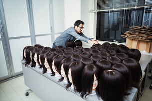 Bearded man wearing glasses standing indoors, arranging mannequin heads with brown wigs.の写真素材 [FYI02858946]