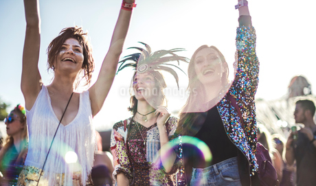 Three smiling young women at a summer music festival face painted, wearing feather headdress, arms rの写真素材 [FYI02858956]