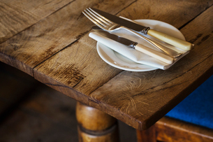 Close up high angle view of plate with knives and fork and a serviette on a rustic wooden table.の写真素材 [FYI02858969]