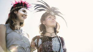 Two young women at a summer music festival faces painted, wearing feather headdresses.の写真素材 [FYI02858973]