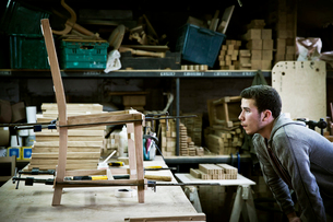 A man working in a furniture maker's workshop assembling a chair.の写真素材 [FYI02858977]