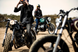 Three men sitting on cafe racer motorcycles on a dusty dirt road.の写真素材 [FYI02858990]