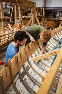 Two men in a boat-builder's workshop, working together on a wooden boat hull.の写真素材 [FYI02859001]
