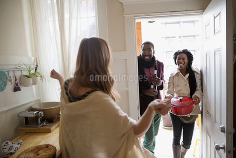 Woman greeting friends arriving for potluck dinner partyの写真素材 [FYI02859013]