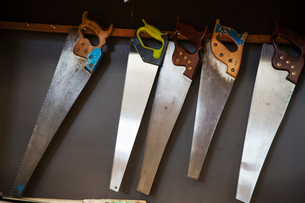 Close up of hand saws hanging on a wall in a boat-builder's workshop.の写真素材 [FYI02859017]